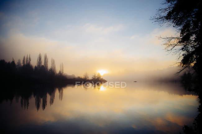 Reflection of trees in water at sunset, Bainbridge, Washington, United States — Stock Photo
