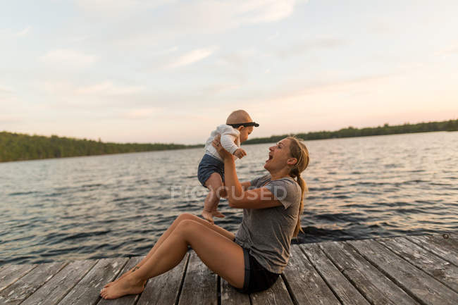 Mother sitting on lake pier holding up baby daughter — Stock Photo