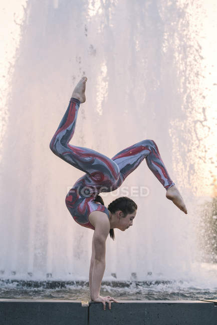 Teenage girl beside fountain balancing on hands in yoga position — Stock Photo