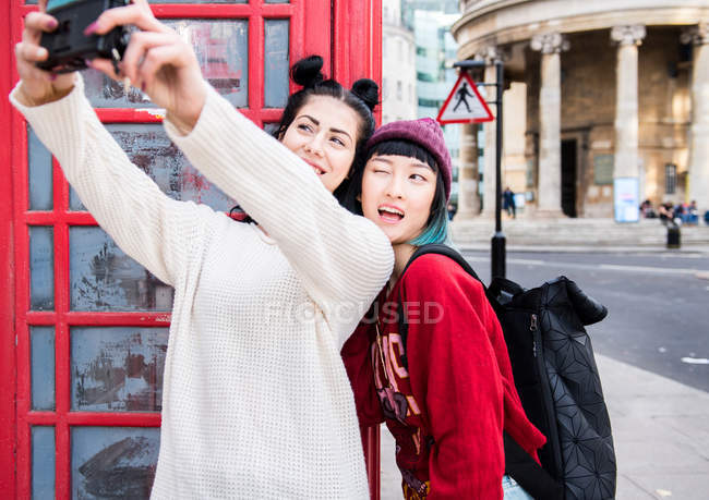 Two young stylish women taking selfie by red phone box, London, UK — Stock Photo