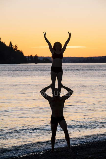 Пара практикующих йогу на пляже на закате — стоковое фото