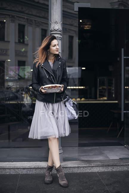 Портрет жінка в вулиці холдингу блюдо їжі — стокове фото