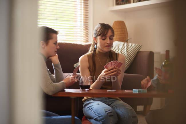 Amis femmes jouant dans les cartes dans le salon — Photo de stock