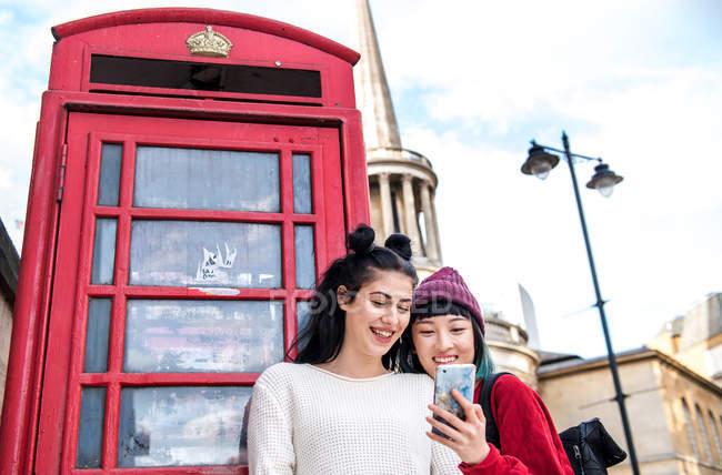 Duas jovens mulheres elegantes olhando para o smartphone por caixa de telefone vermelha, Londres, Reino Unido — Fotografia de Stock