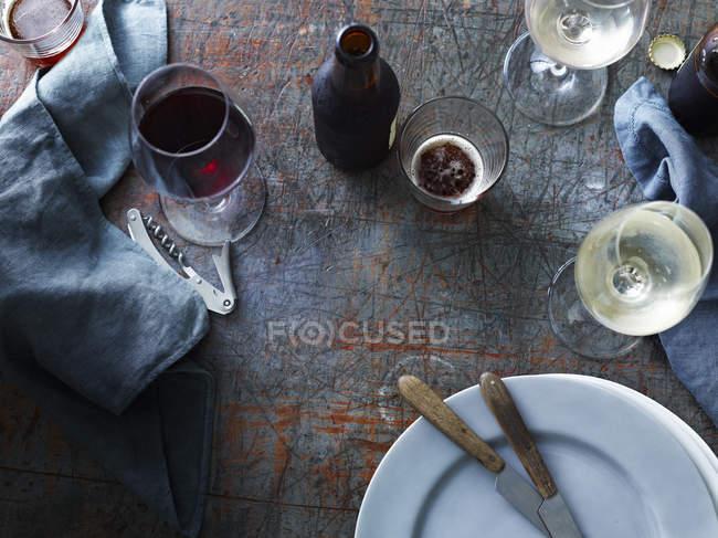 Cerveja em garrafa com copos de vinho vermelhos e brancos na tabela, visão aérea — Fotografia de Stock