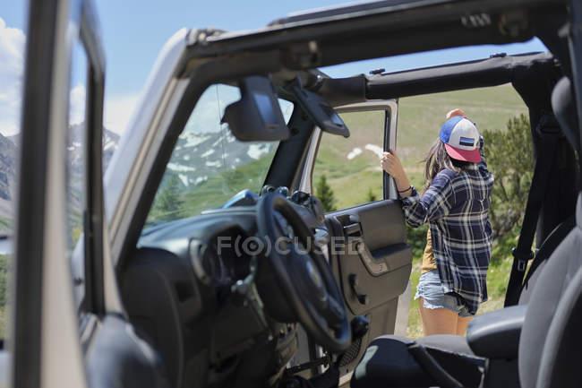 Junge Frau von Geländewagen Blick auf die Rocky Mountains, Breckenridge, Colorado, Usa — Stockfoto