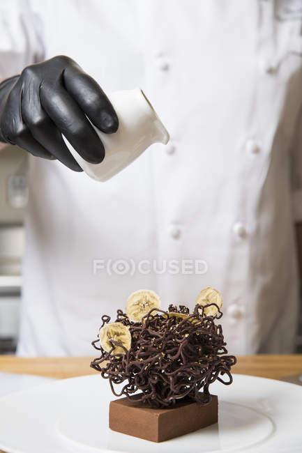Chef, verser la crème sur décoration de gâteau de chocolat nid sur gâteau — Photo de stock