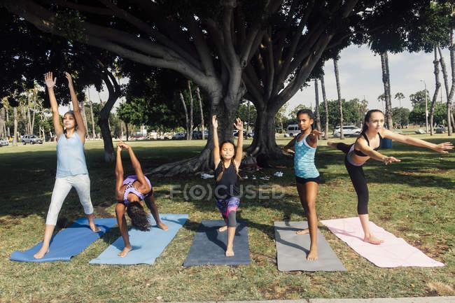 Девочки и школьницы-подростки практикуют йогу воин позируют на школьном игровом поле — стоковое фото