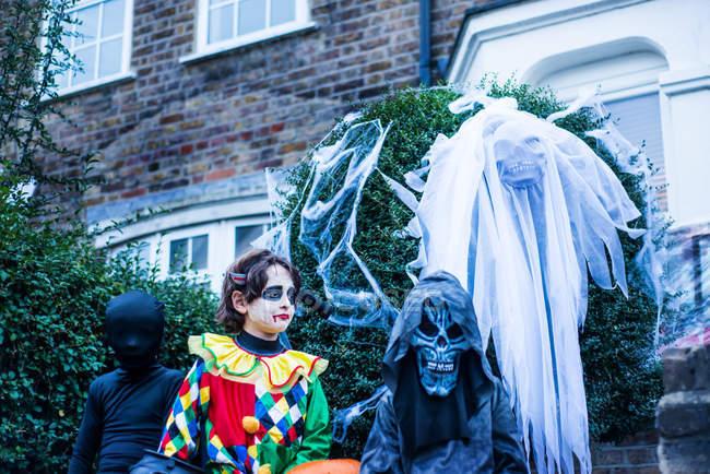 Jeunes garçons vêtus de costumes d'Halloween, à côté de la maison, en train de tricher ou de traiter — Photo de stock