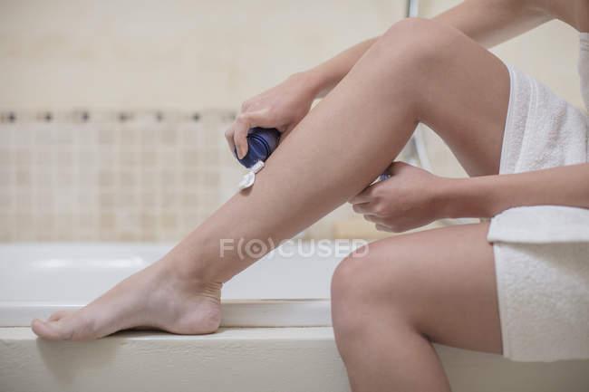 Jeune femme, appliquer la mousse à raser à pied dans la salle de bain — Photo de stock