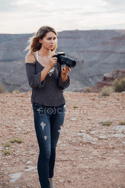 Young woman outdoors holding camera, Mexican Hat, Utah, USA — Stock Photo