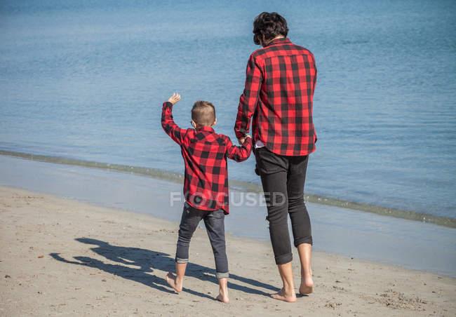 Батько і син, прогулянки по пляжу з тримаючись за руки — стокове фото