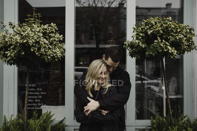 Portrait of man hugging woman in street — Stock Photo