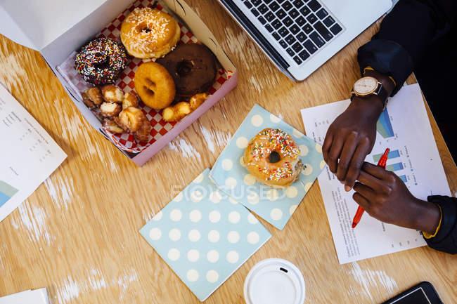 Vue aérienne de boîte de gâteau de beignets sur le Bureau de la femme de rognée — Photo de stock