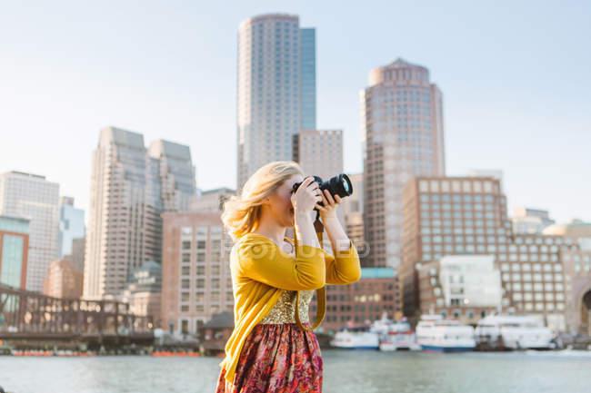 Jovem mulher fotografando de quayside, Boston, Massachusetts, EUA — Fotografia de Stock