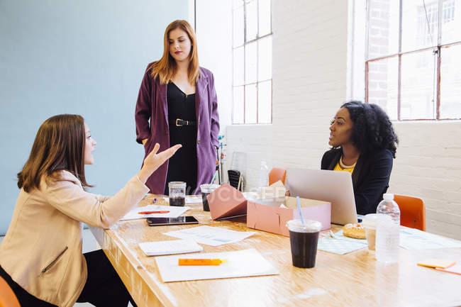 Жіночий колег у сучасні офісні, маючи обговорення — стокове фото