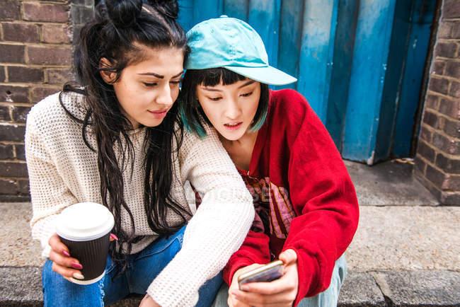 Duas jovens mulheres sentadas na calçada e olhando para o smartphone — Fotografia de Stock