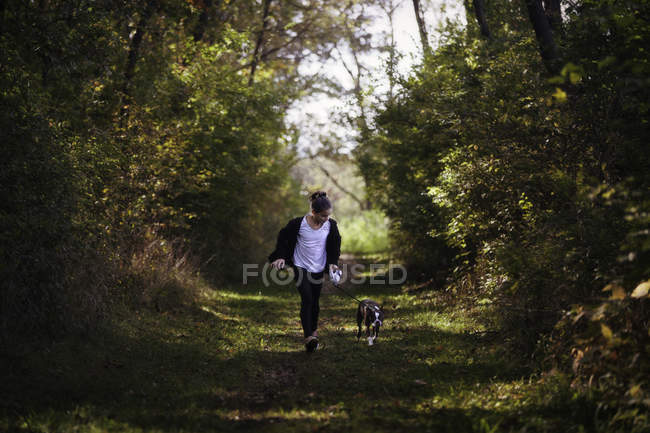 Young girl walking with dog in rural setting — Stock Photo