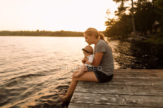 Mother sitting on pier with baby daughter looking down at  lake — Stock Photo