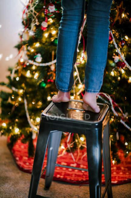 Enfant sur le tabouret pour atteindre vers le haut pour décorer le sapin de Noël — Photo de stock