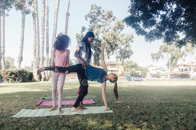 Девочки и девочки-подростки практикуют йогу стоя на полу-лунной позе на школьном игровом поле — стоковое фото