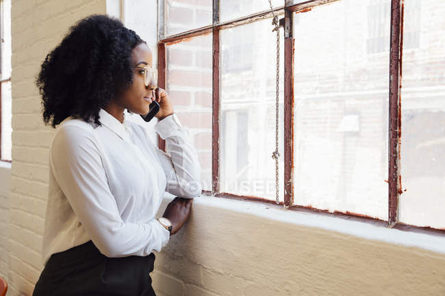 Woman in industrial office building making telephone call — Stock Photo