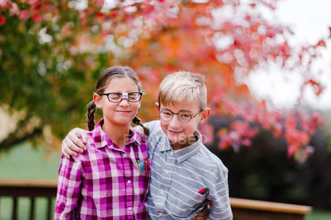 Fratelli con le braccia intorno vestite da nerd — Foto stock