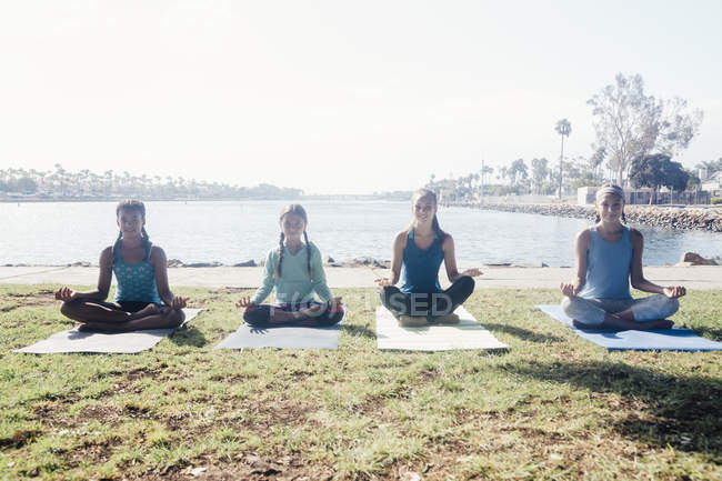 Schoolgirls practicing yoga lotus pose by lakeside on school sports field — Stock Photo