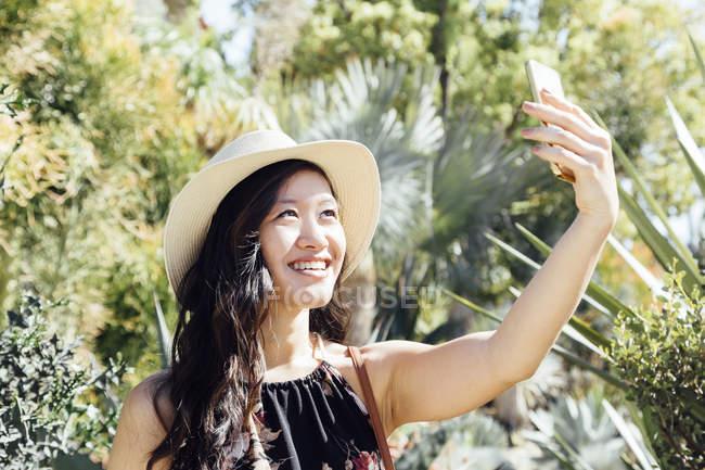 Mujer joven al aire libre, tomando selfie en jardín ornamental - foto de stock