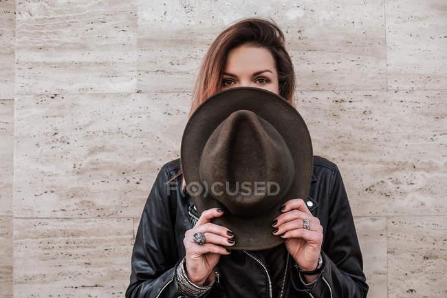Portrait of woman hiding face behind hat — Stock Photo