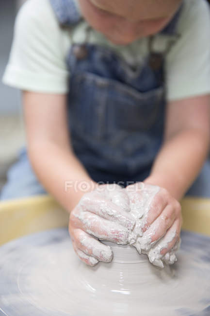 Close up de menino moldar argila na roda de oleiro — Fotografia de Stock