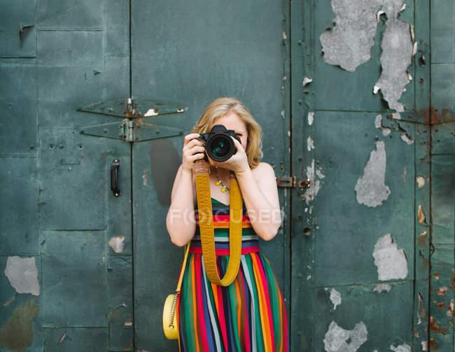 Jovem mulher em vestido listrado na frente da porta industrial tirar foto — Fotografia de Stock