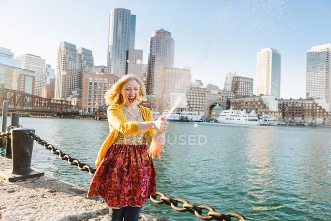 Young woman opening champagne on quayside, Boston, Massachusetts, USA — Stock Photo