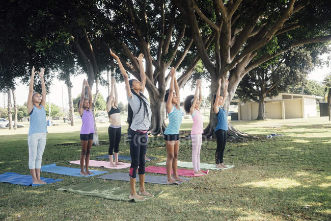 Школьницы, практикующие йогу, позируют на школьной спортивной площадке — стоковое фото