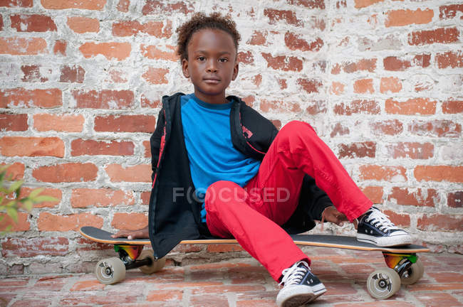 31425fa0951 Portrait of young boy sitting on skateboard — Stock Photo