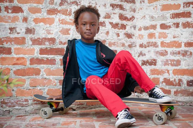 Портрет мальчика, сидящего на скейтборде — стоковое фото