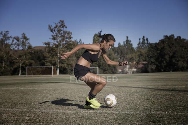 Junge Frau am Fußballplatz, Fußball spielen — Stockfoto
