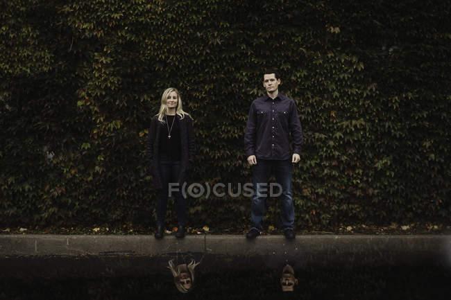 Ritratto di coppia adulta in piedi davanti al fogliame — Foto stock
