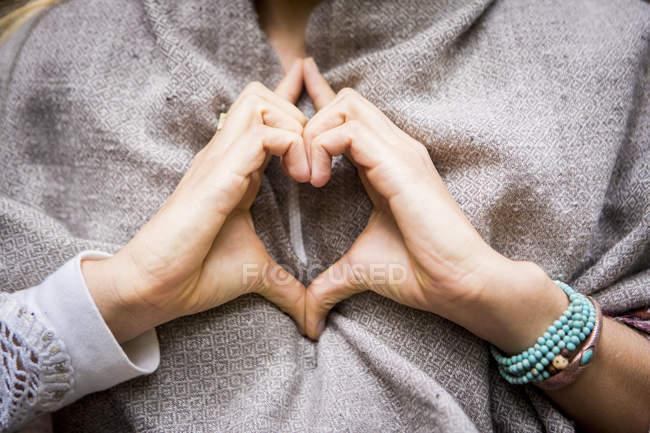 Mãos de mulher fazendo formato de coração — Fotografia de Stock