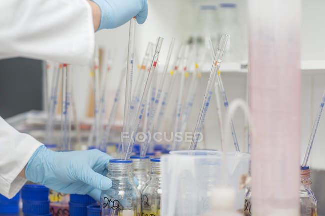 Laborangestellte nimmt mit langer Pipette Farbstoff aus Becher — Stockfoto