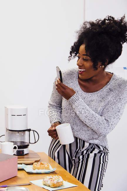 Femme tenant la tasse de café et de la prise de photo sur smartphone — Photo de stock