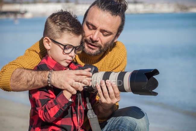 Padre e figlio all'aperto, padre che insegna al figlio ad usare la macchina fotografica — Foto stock
