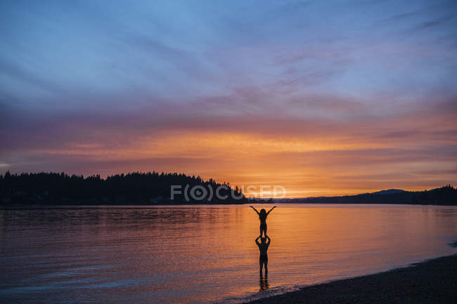 Casal praticando ioga na praia ao pôr do sol — Fotografia de Stock