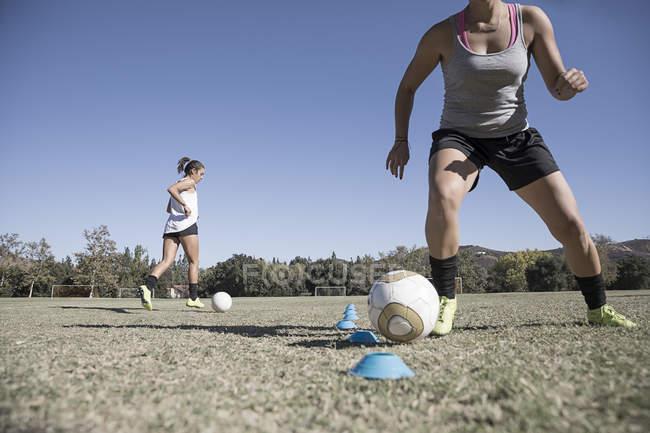 Deux jeunes femmes dribble de ballons de football sur le terrain de football — Photo de stock