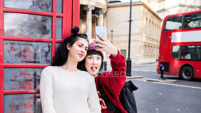 Due giovani donne alla moda che scattano selfie dalla cabina telefonica rossa, Londra, Regno Unito — Foto stock