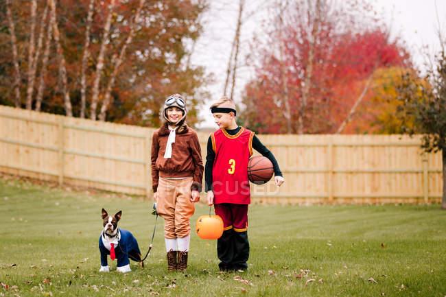 Portrait d'un garçon, d'une sœur jumelle et de Boston terrier portant des costumes d'Halloween dans le jardin — Photo de stock