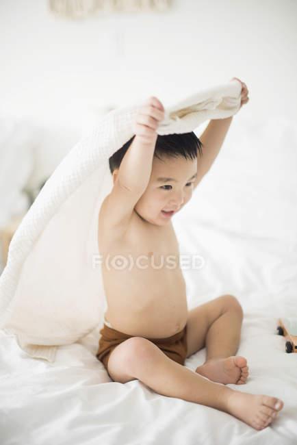 Маленький хлопчик з капюшоном рушник в ліжку — стокове фото