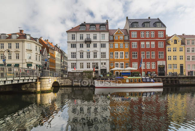 Moored boat and bridge with colorful houses on Nyhavn canal, Copenhagen, Denmark — Stock Photo
