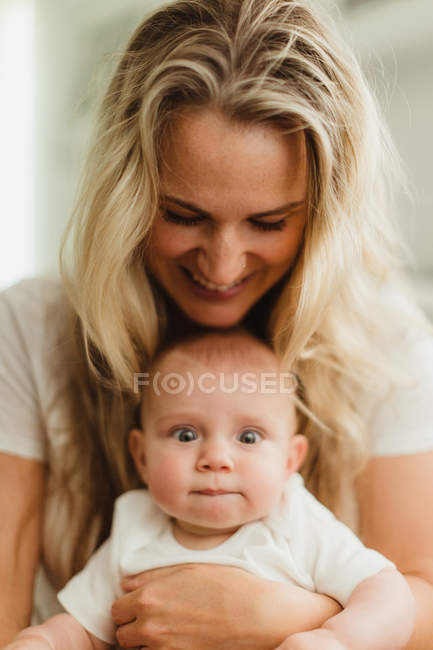 Portrait of baby girl sitting on mother's lap — Stock Photo