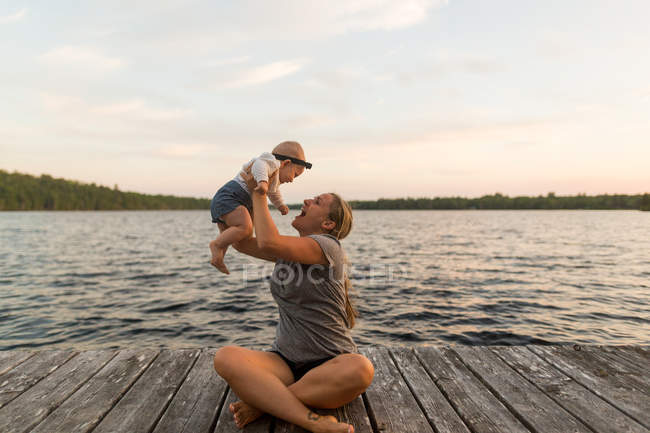 Mother sitting cross legged on lake pier holding up baby daughter — Stock Photo